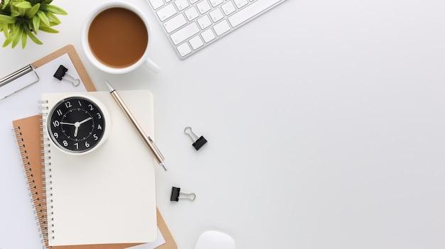 컴퓨터와 사무용품이 있는 위쪽 흰색 나무 작업 공간 책상. 빈 노트북, 키보드, 녹색 잎, 커피 컵이 있는 평평한 작업 테이블. 광고 콘텐츠를 위한 공간을 복사합니다.