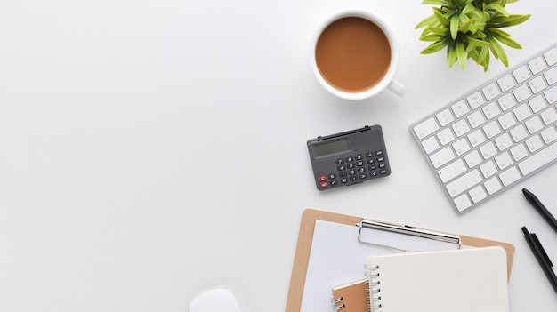 Вид сверху белый деревянный рабочий стол офисный стол с компьютером и канцелярскими товарами. плоский рабочий стол с пустой записной книжкой, клавиатурой, зеленым листом и кофейной чашкой. скопируйте место для вашего рекламного контента.