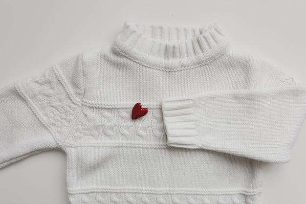 Вид сверху белый шерстяной свитер с красным сердцем. плоская планировка
