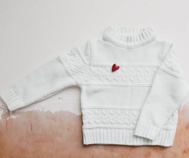 Top view white woolen sweater with a red heart. flat lay