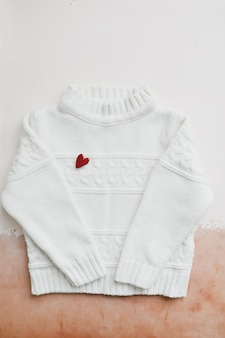 Top view white woolen sweater with a red heart.
