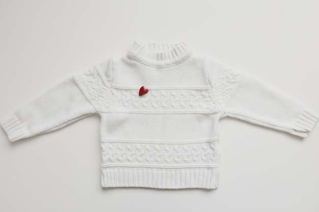 Top view white woolen sweater with a red heart
