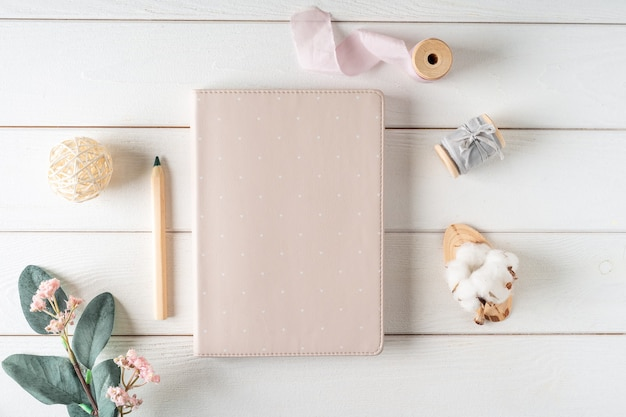 Top view of white working table background with blank paper notebook, nature cotton. flat lay