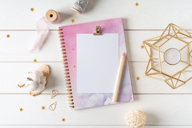 Top view of white working table background with blank paper notebook, nature cotton.