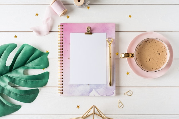 Top view of white working table  with blank paper notebook, cup of coffee. flat lay monstera leaf, golden paper binder clips. notepad and pen.