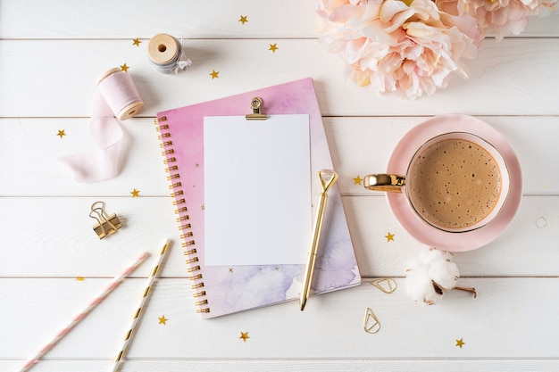 Top view of white working table  with blank paper notebook, cup of coffee. flat lay peonies flowers, golden paper binder clips. notepad and pen.