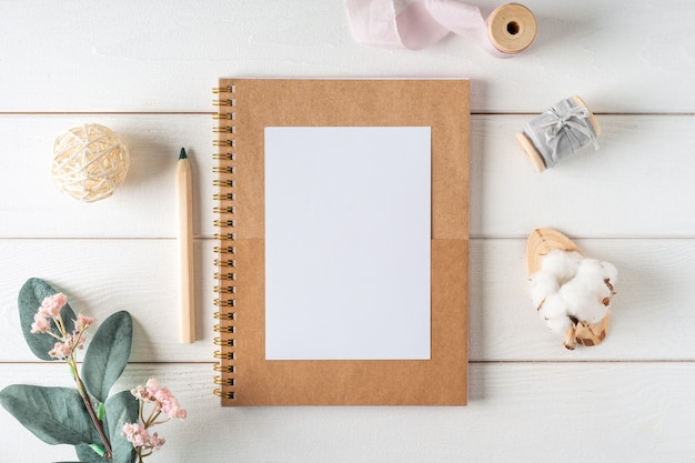 Top view of white working table  with blank paper notebook, nature cotton. flat lay green leaf, flowers, golden paper binder clips. notepad and pen.