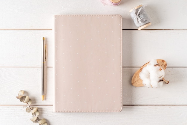 Top view of white working table  with blank paper notebook, nature cotton. flat lay still life candle, golden paper binder clips. notepad and pen.