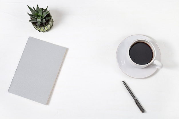 Top view of white working table with closed copybook, white cup of coffee, pen and green succulent plant. work space for school or office. copy space. flat lay.