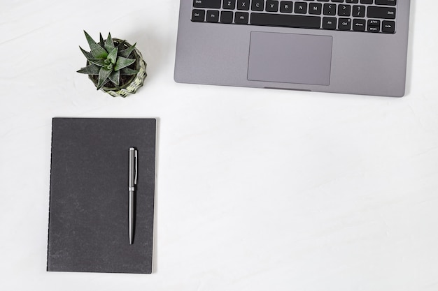 Top view of white working table with laptop, dairy, pen and succulent plant
