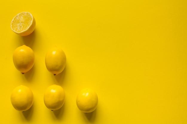トップビュー全体とスライスした熟したレモン、黄色の表面、健康とビタミンの概念上のいくつかの行にレイアウト