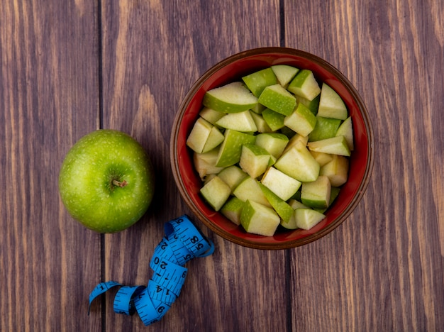 Top view of whole apple with chopped apple slices on a red bowl on a wooden surface