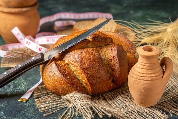 Vista dall'alto di pane nero intero e tagliato e punte su ceramiche di misuratore di asciugamano marrone su superficie di colori scuri