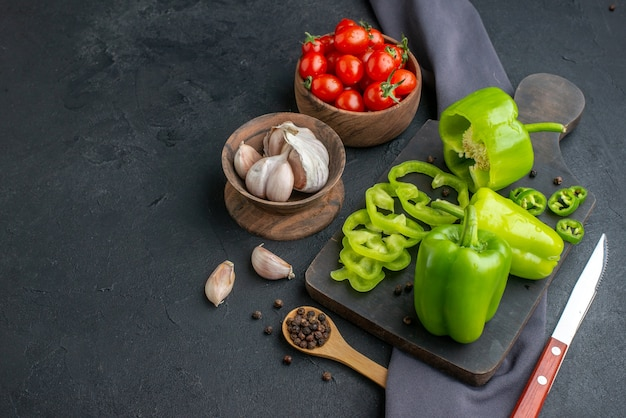 Vista dall'alto di peperoni verdi tagliati interi su tagliere di legno nero coltello su asciugamano pomodori garlics in ciotole su superficie nera in difficoltà