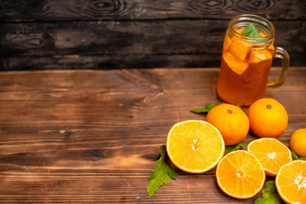 Top view of whole and cut fresh oranges with leaves and natural juice in a glass on the left side on a brown background