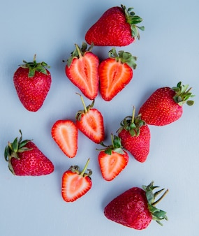 Top view of whole and cut strawberries on blue surface