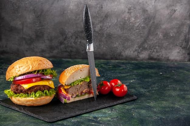 Vista dall'alto del taglio intero di vari gustosi panini e pomodori con coltello a gambo sul vassoio nero sul lato destro sulla superficie di colore scuro della miscela