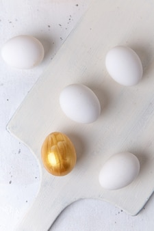Top view of whole eggs on white surface