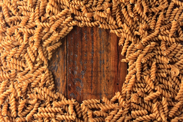 Top view of the whole fusilli pasta, on a wooden background.