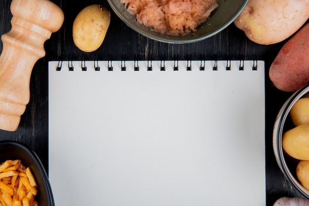 Vista superiore di intere patate grattugiate e fritte intorno al blocco note con sale su superficie di legno con lo spazio della copia