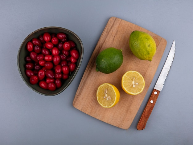 Top view of whole and half cut lemons on cutting board and bowl of cornel berries with knife on gray background