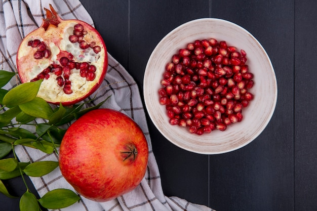Top view whole half and peeled pomegranate with a branch of leaves and a checkered towel on a black table