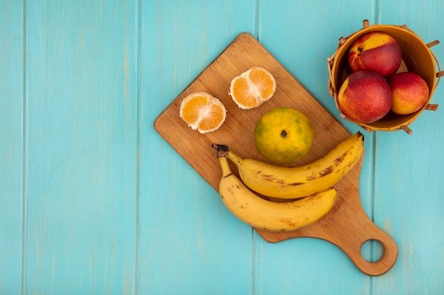 Top view of whole and half tangerines on a wooden kitchen board with bananas with peaches on a bucket on a blue wooden wall with copy space