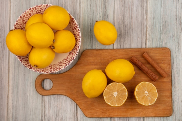 Top view of whole lemons on a bowl with lemons isolated on a wooden kitchen board with cinnamon sticks on a grey wooden wall