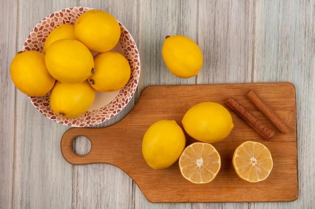 Vista dall'alto di limoni interi su una ciotola con limoni isolati su una tavola da cucina in legno con bastoncini di cannella su una parete di legno grigia
