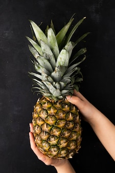 Top view of whole pineapple being held by woman hands on black surface