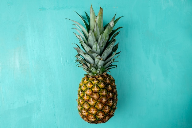Top view of whole pineapple on blue surface