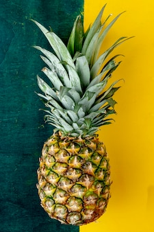 Top view of whole pineapple on green and yellow surface