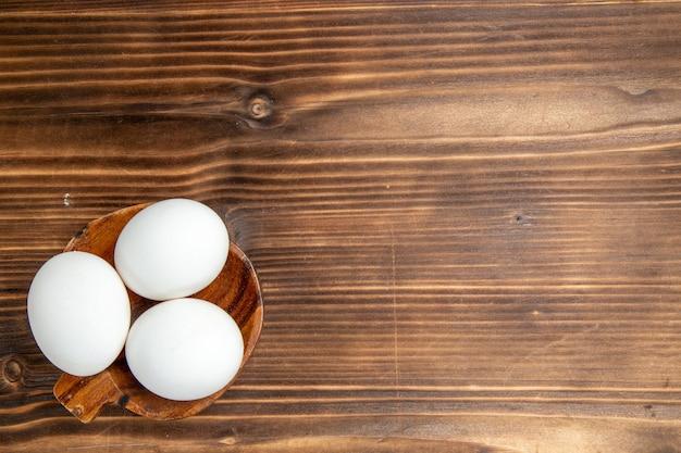 茶色の木製の背景の食事食品朝食木材の上面図全生卵