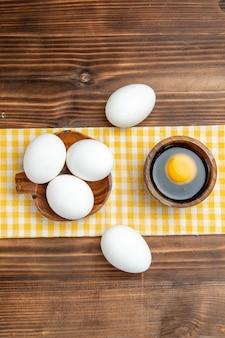 茶色の木製の表面に生卵全体を上面図食品朝食木製卵