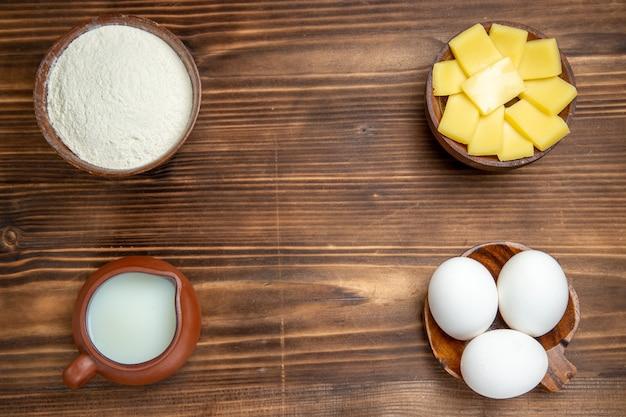 Вид сверху целые сырые яйца с сырной мукой и молоком на коричневом деревянном столе, продукты, тесто из яичного теста