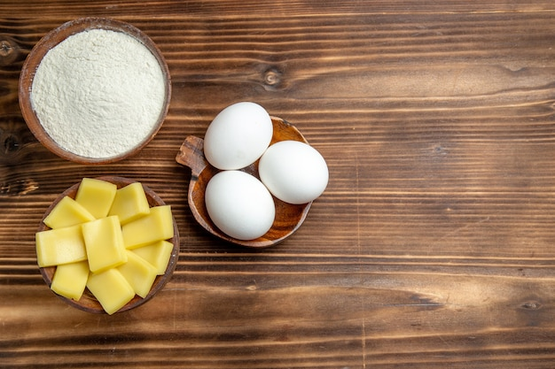 上面図茶色のテーブル卵生地小麦粉ダスト製品に小麦粉とチーズを入れた生卵全体 無料写真