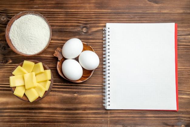 茶色のテーブルに小麦粉とチーズを入れた生卵全体の上面図卵生地小麦粉ダスト製品
