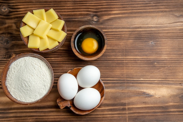 Вид сверху целые сырые яйца с мукой и сыром на коричневом столовом яичном тесте, мучной пыли