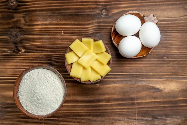 Вид сверху целые сырые яйца с мукой и сыром на коричневом столе, яйца, тесто, мучная пыль, продукт