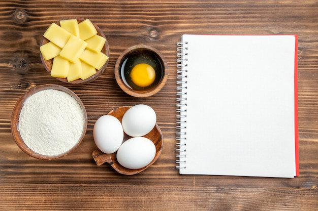 Вид сверху целые сырые яйца с мукой и сыром на коричневом деревянном столе, яичное тесто, мучная пыль
