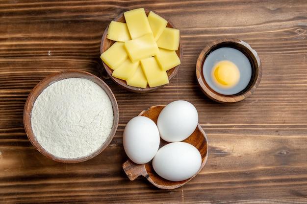 Вид сверху целые сырые яйца с мукой и сыром на коричневом столе, яйцо, тесто для завтрака, мучная пыль