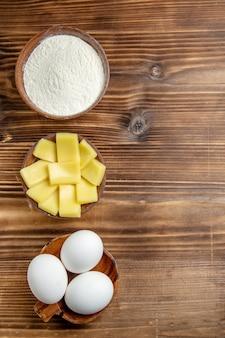 Вид сверху целые сырые яйца с мукой и сыром на коричневом столе, продукты из муки из яичного теста