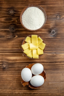 Top view whole raw eggs with flour and cheese on the brown table eggs dough flour dust product