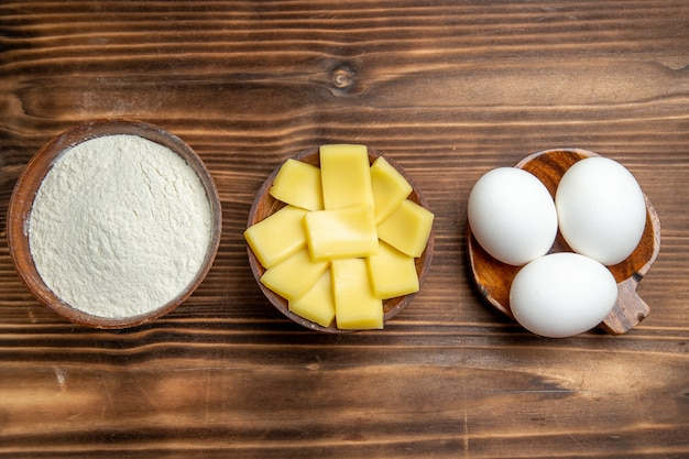 Top view whole raw eggs with flour and cheese on brown table eggs dough flour dust products