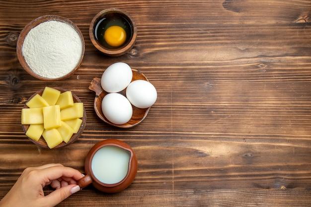 Vista dall'alto intere uova crude con farina di latte e formaggio sui prodotti in polvere di farina di farina di pasta all'uovo da tavola marrone