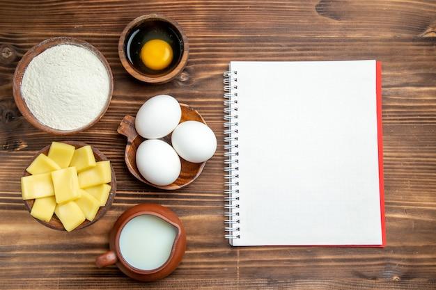 Vista dall'alto intere uova crude con farina di latte e formaggio su tavola marrone uova pasta farina di prodotti in polvere