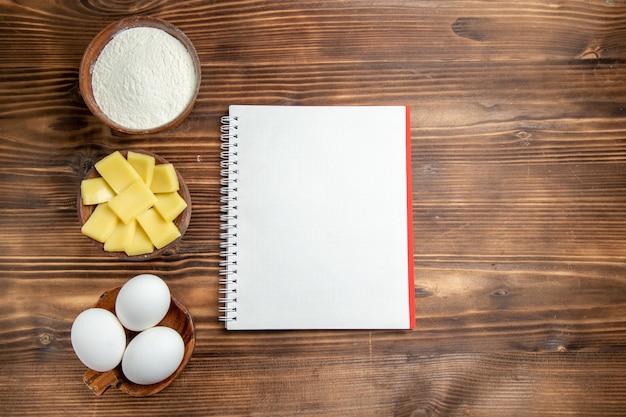 Вид сверху целые сырые яйца с блокнотом из муки и сыром на коричневом столовом яичном тесте, мучной пыли