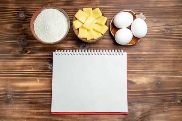 Вид сверху целые сырые яйца с блокнотом из муки и сыром на коричневом столе, яйца, тесто, мучная пыль