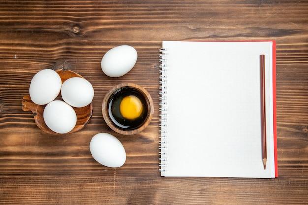 Uova crude intere di vista superiore con il blocco note sull'uovo di legno della colazione dell'alimento del pasto della superficie di legno marrone