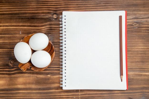 Вид сверху целые сырые яйца с блокнотом на коричневой деревянной поверхности